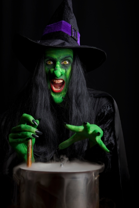 A scary witch stirring her smoking cauldron. Isolated on black background with low key lighting.