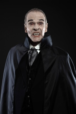 Dracula with black cape showing his scary teeth. Vamp fangs.
